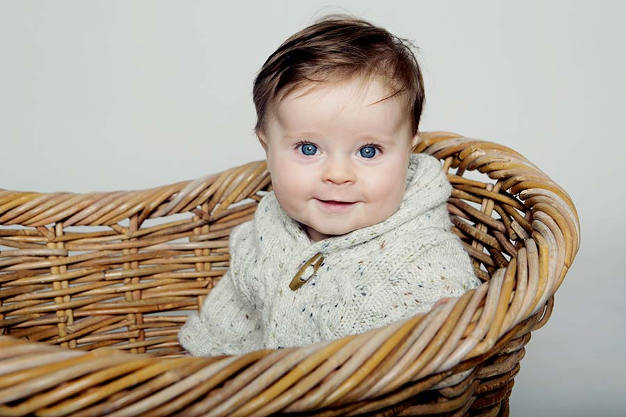 Smiling baby in a basket - Studio Photography in Oxfordshire